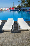Swimming pool surrounded by chairs Royalty Free Stock Image