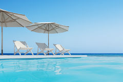 Swimming pool with three deck chairs, umbrellas. Three white deck chairs are standing under beach umbrellas near a swimming pool. A cloudless blue sky is above Stock Photography