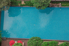 Swimming pool with trees and umbrellas from a top down view from the rooftop or high floor. Trees and reflections make for a nice Royalty Free Stock Photo