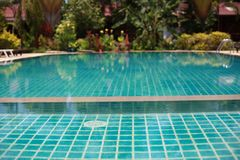 Swimming pool in tropical garden with bamboo bungalow - paradise for tourists. Stock Photography