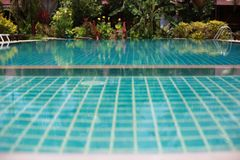 Swimming pool in tropical garden with bamboo bungalow - paradise for tourists. Royalty Free Stock Image