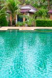Swimming pool in a tropical hotel with palms and bungalows. Swimming pool in a tropical hotel with green palms and bungalows on background Stock Photos