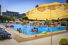 Swimming pool in tropical resort hotel. Yellow umbrella on blurred background of bathing tourists in pool on bright sunny day. On vacation stock photography