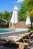 Swimming pool in tropical resort. Swimming pool and sun beds in tropical garden , Thailand Stock Photo