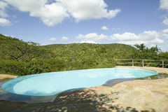 Swimming pool with turquoise water surrounded by the hills of North Kenya, Africa at the Lewa Wildlife Conservancy Stock Photo