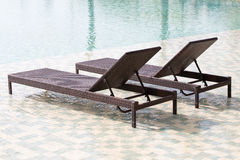 Swimming pool and two deck chairs, close up Stock Images