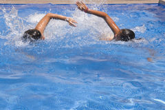 Swimming in the pool. Two teenagers swimming in the pool hard from home Royalty Free Stock Photography