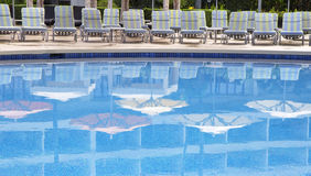 Swimming pool with umbrellas reflections Stock Images