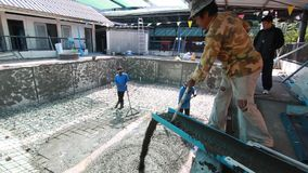 Swimming pool under construction, being sprayed on rebar for new swimming pool. Thailand stock footage
