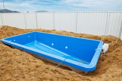 Swimming pool under construction. Installation plastic fiberglass pool in the ground at house backyard. Construction site Royalty Free Stock Images