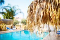 Swimming pool under the straw umbrella Royalty Free Stock Photos