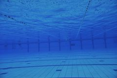 Swimming pool underwater. Sport swimming pool  underwater with blue color and swimmers Stock Photos