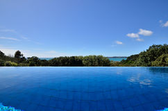 Infinity swimming pool with an ocean view. A very blue swimming pool overlooking the ocean royalty free stock photo