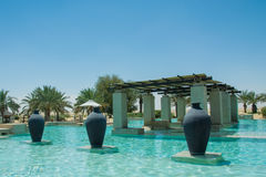 Swimming pool view with three jugs at the desert arabian resort Royalty Free Stock Photos