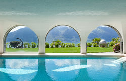 Swimming pool of a villa, interior. Luxury villa with indoor swimming pool, arched windows Stock Photography