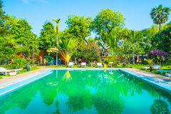 Swimming pool and villa in tropical garden Stock Photos