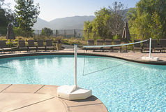 Swimming pool with volleyball net. Luxury swimming pool with net for volleyball, hills beyond Royalty Free Stock Photos