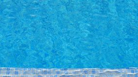 Swimming pool water background with mosaic tiles at one end, texture of water surface with ripple effect royalty free stock photography