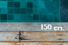 Swimming pool water depth sign on wooden platform Royalty Free Stock Photos