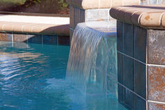 Swimming Pool Waterfall. The waterfall of a swimming pool circulates the water between a spa and the main pool. This keeps the temperature of both the spa and Stock Photos
