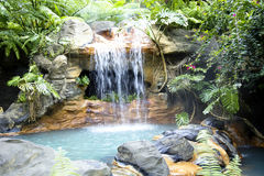 Swimming pool with a waterfall and hot thermal water Stock Photos