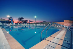 Swimming Pool with waterside during twilight Stock Photos