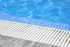 Swimming pool white grating grille with clear blue water and grey tiles. Stock Images