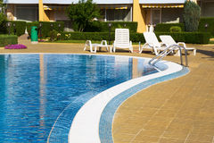 Swimming pool with white sunbeds at a hotel Royalty Free Stock Photo