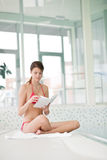 Swimming pool - woman relax with book. Sitting down Stock Image