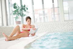 Swimming pool - woman relax with book. Lying down Royalty Free Stock Photography