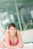 Swimming pool - woman relax listen to music. With ear buds Royalty Free Stock Photography
