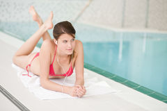 Swimming pool - woman relax listen to music. Swimming pool - beautiful woman relax listen to music with ear buds Royalty Free Stock Image