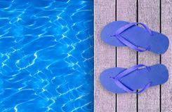 Swimming pool, wooden deck and blue beach shoes Royalty Free Stock Images