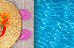 Swimming pool, wooden deck and pink beach shoes with hat Stock Photography