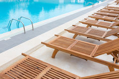 Swimming pool with wooden sunbeds. Royalty Free Stock Image