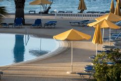 Swimming pool with yellow umbrellas on the beach of the hotel complex. Of the Rhodos Island Stock Photo