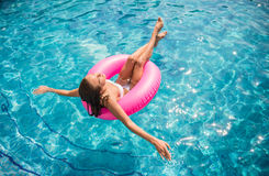 Swimming pool. Young beautiful woman is relaxing in swimming pool with rubber ring Stock Image