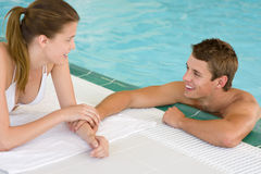 Swimming pool - young loving couple hold hands Royalty Free Stock Images