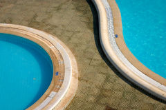 Swimming pools. An aerial view of a pair of ornate hotel outdoor swimming pools reflecting the hot North African sun in Tunisia royalty free stock images