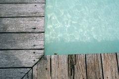 Swimming Pools edge wooden decking background. Worn wooden boards at edge of sparkling swimming pool royalty free stock image