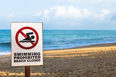 Swimming prohibited, beach closed warning sign on a beach. With blue cloudy sky and sandy beach in background, room for text or copyspace royalty free stock photos