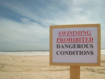 Swimming prohibited, dangerous conditions, sign on beach Stock Images