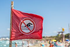 Banner for a bathing prohibition on a full beach stock images