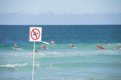 Swimming prohibited sign with surfer in ocean Stock Photos