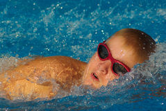 Swimming Race. Boy swimming is frozen in time in what looks like ice, but is really water Stock Photo
