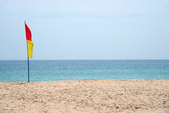 Swimming safety flags on the beach with blue sky. Royalty Free Stock Images