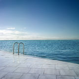 Swimming in the sea. Baths area in Barcelona coast. Evocative image of a large pool Royalty Free Stock Image