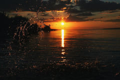Swimming and splashing on summer beach over sunset. Royalty Free Stock Image