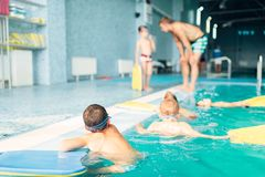 Children swimming in pool. Swimming sports activity. Children swimming in pool. Healthy and happy childhood concept. Kids in water with planks for swimming Royalty Free Stock Photography