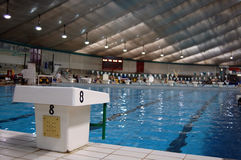 Swimming starting block with pool in background. Starting block, with number 8, in foreground, with 25 metre swimming pool visible in background stock image